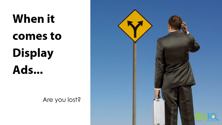 Image: A man in a suit, holding a silver case, scratches his head in front of a yellow road sign with 2 diverging arrows pointed upwards in opposite directions. Text reads When it comes to Display Ads...Are you lost?