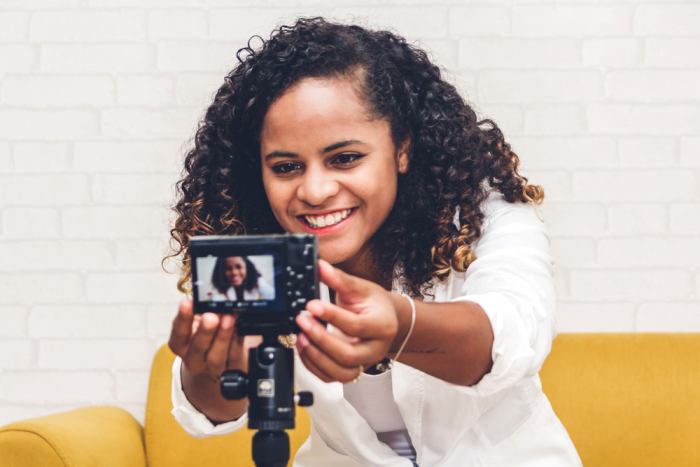 african american woman in white jacket seated on a  yellow sofa adjusts a video camera on a tripod
