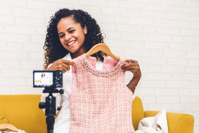african american woman in a white jacket seated on a yellow couch holds up pink wool houndstooth print dress in front of her to camera and smiles