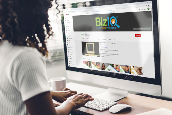 african american woman in white t-shirt types on computer while browsing youtube with biziq logo and channel on screen