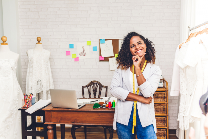 african american woman business owner in white jacket in her office surrounded by dresses, looking up to think about video for YouTube