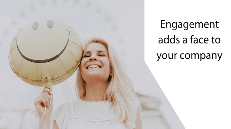 Image: a smiling blond woman with long hair and a white shirt holds a yellow, Mylar smiley face balloon sub header title text reads Engagement adds a face to your company